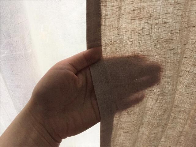 リフリンのリネンカーテンのシワを伸ばしていいる様子生地が湿って色が変わるくらい水をかけ手でシワを矯正